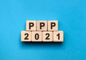 PPP - text concept on wooden cubes with gradient blue background.